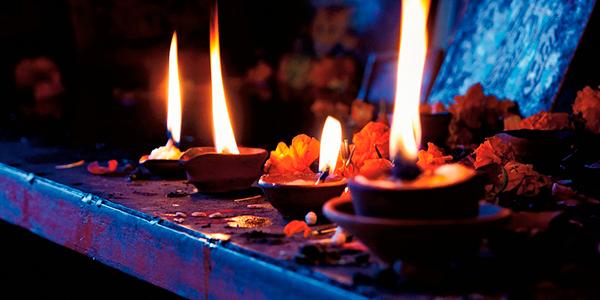 Foto tenue de un altar de brujo,con pétalos de flores y cuatro velas encendidas.